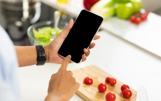 Black girl using smartphone with blank screen in the kitchen